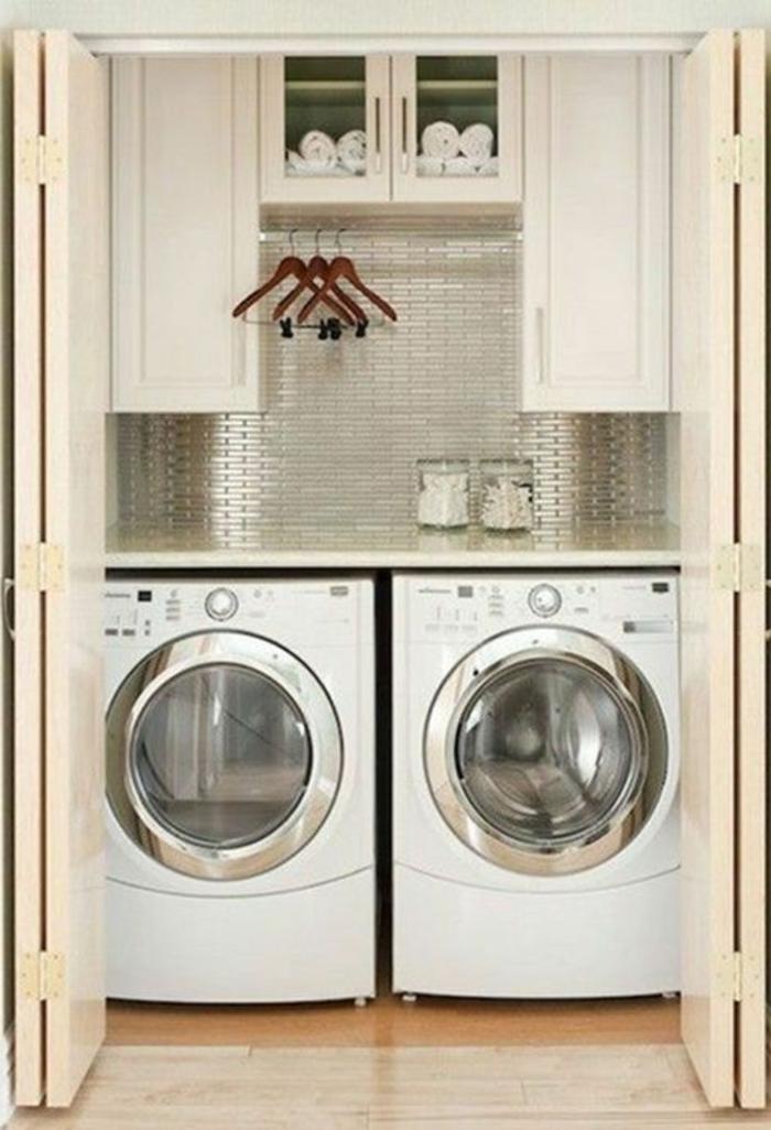 aménagement buanderie,tuiles luisantes lurales, lave-linge et sèche linge, barre métallique pour les vêtements lavés