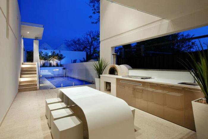 un patio moderne avec espace piscine et une cuisine d'extérieur aux lignes élégantes