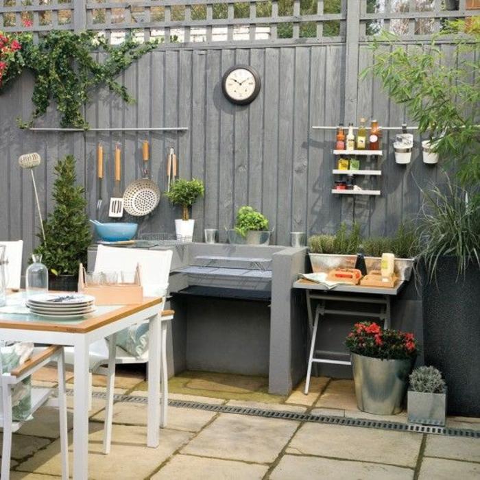 une cuisine d'extérieur en béton en harmonie avec la palissade grise