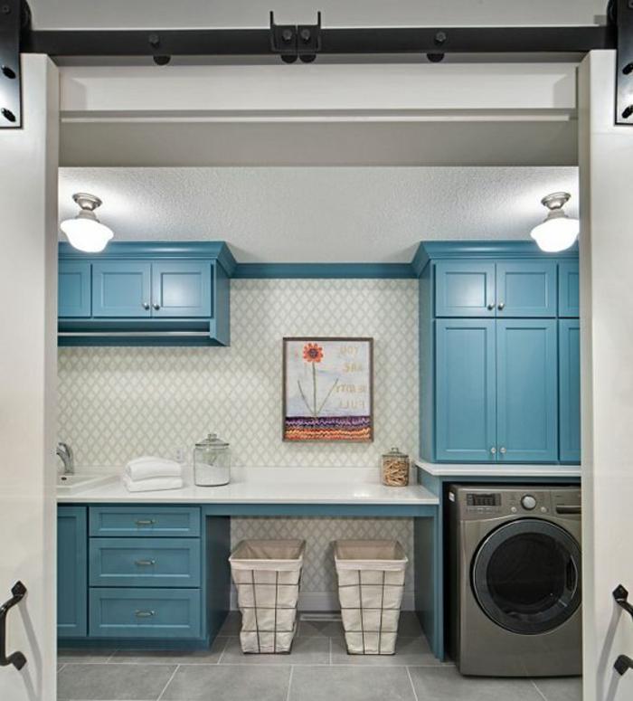 aménager sa buanderie, carrelage déco mural, placards bleus et deux paniers sous le plan de travail
