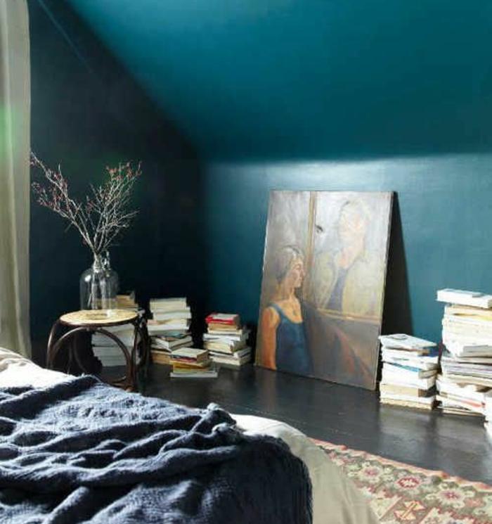 chambre mansardée, couleur mur bleu paon, parquet en bois gris anthracite, piles de livres, tableau peinture, tapis oriental, couverture de lit gris anthracite