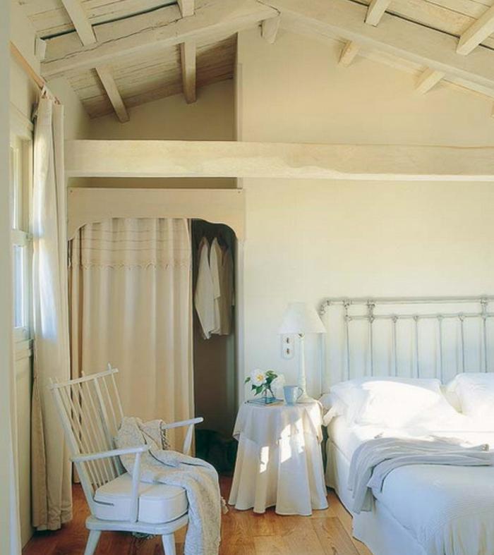 déco chambre sous pente, parquet clair, lit en métal, linge de lit blanc, chaise blanche, toiture poutres blanches, décor piece mansardée tout en blanc