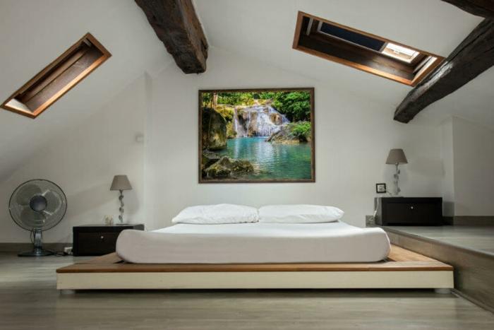 amenager comble, couleur mur blanc, tableau peinture paysage naturel, lit en bois matelas blanc, oreillers blancs, parquet gris