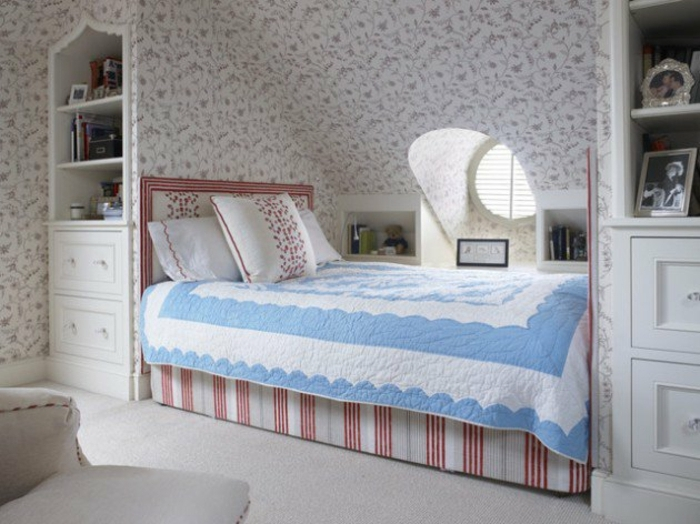amenager comble, chambre à coucher sous les toits, papier peint motif floraux, shabby chic, lit sous pente en rouge et blanc, couverture de lit en blanc et bleu, tapis blanc, meuble mansarde blanc
