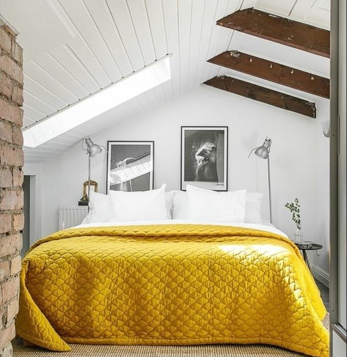 chambre mansardée, couleur mur blanc, deco murale photos en noir et blanc, linge de lit blanc, couverture de lit jaune, poutres apparentes, mur en briques