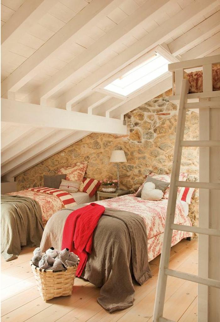 amenagement comble. parquet clair, mur en pierres, totiture en bois blanc, linge de lit en gris, blanc et rouge, panier à jouets
