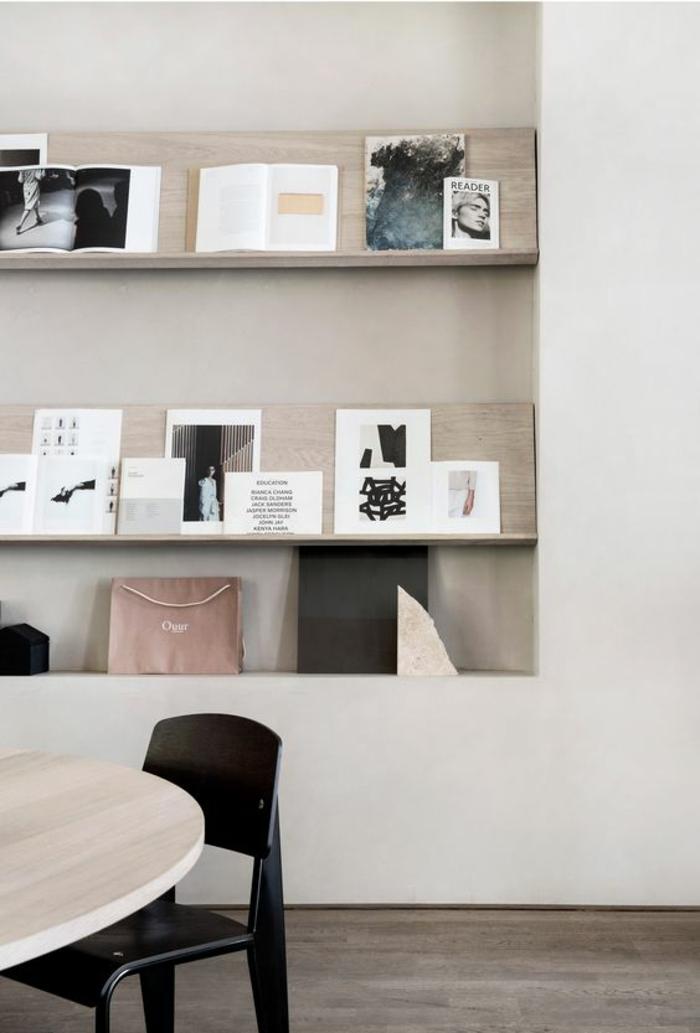 appartement minimaliste, chaise noire et table ovale en bois, étagères en bois