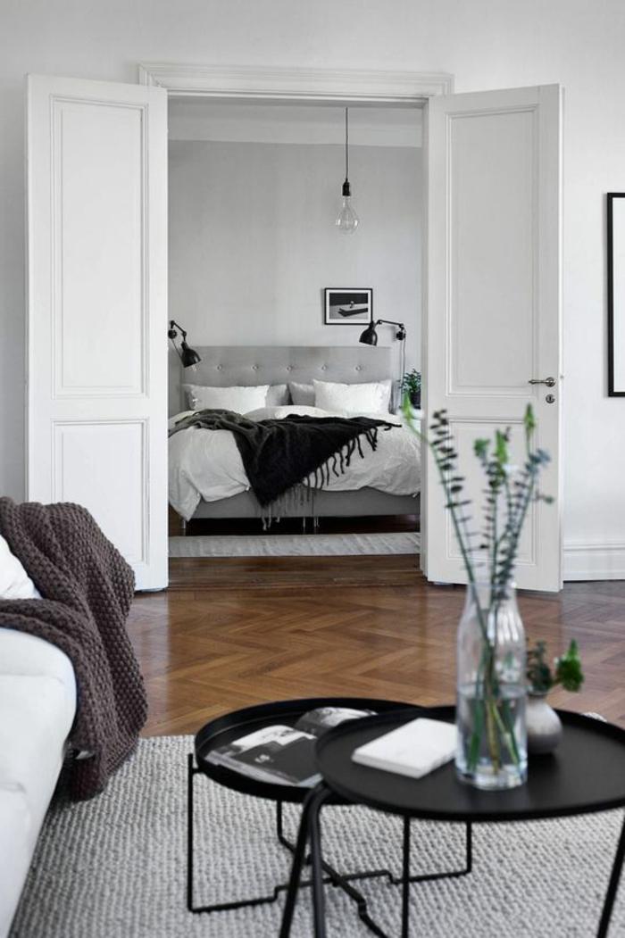appartement minimaliste, chambre à coucher monochrome, sol parqueté, tables basses