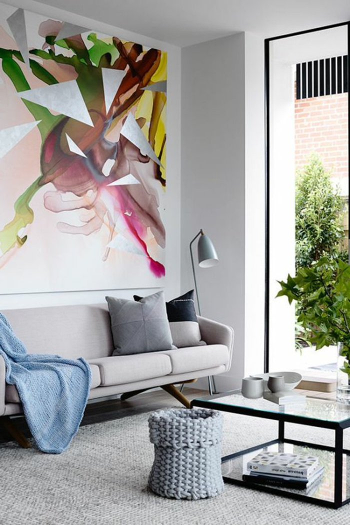 appartement minimaliste, sofa gris, table rectangulaire, tableau abstrait, peinture murale grise