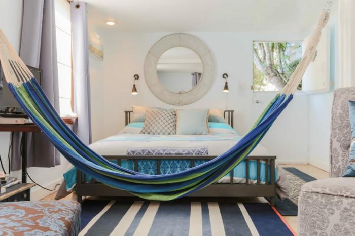 balançoire d intérieur, chambre à coucher en blanc et bleu, miroir mural rond, tapis rayé