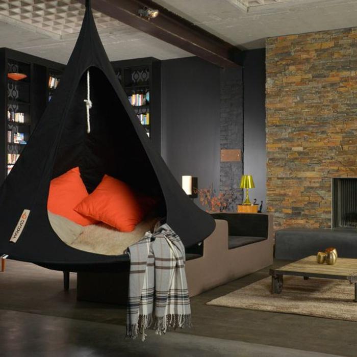 balancoire adulte, balançoire noire avec des plaids en des coussins, salon, mur en pierre apparente