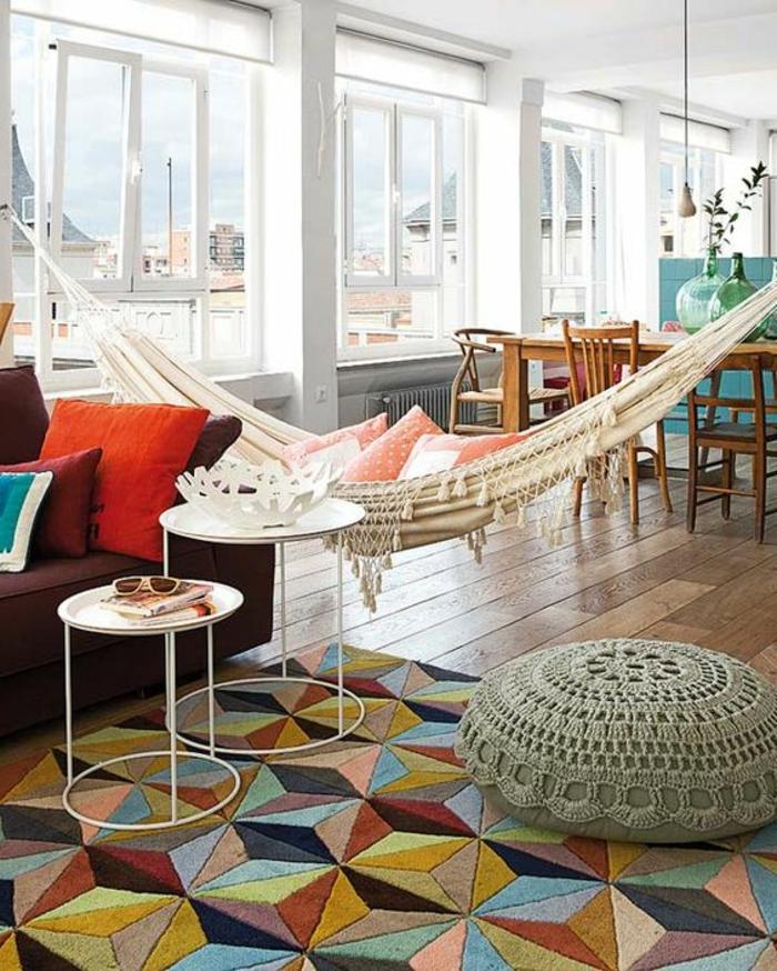 balancoire interieur style boho chic, plusieurs coussins colorés, table à manger dans le salon