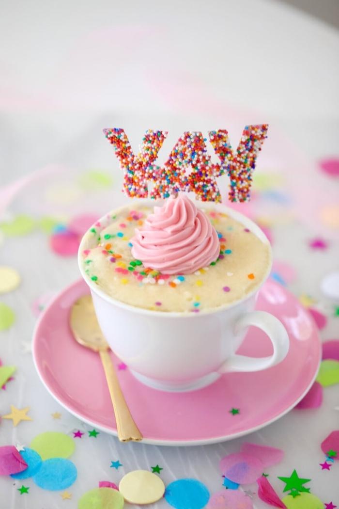mini cake dans une tasse blanche décoré avec arrose arc en ciel et crème rose, exemple patisserie sans oeuf