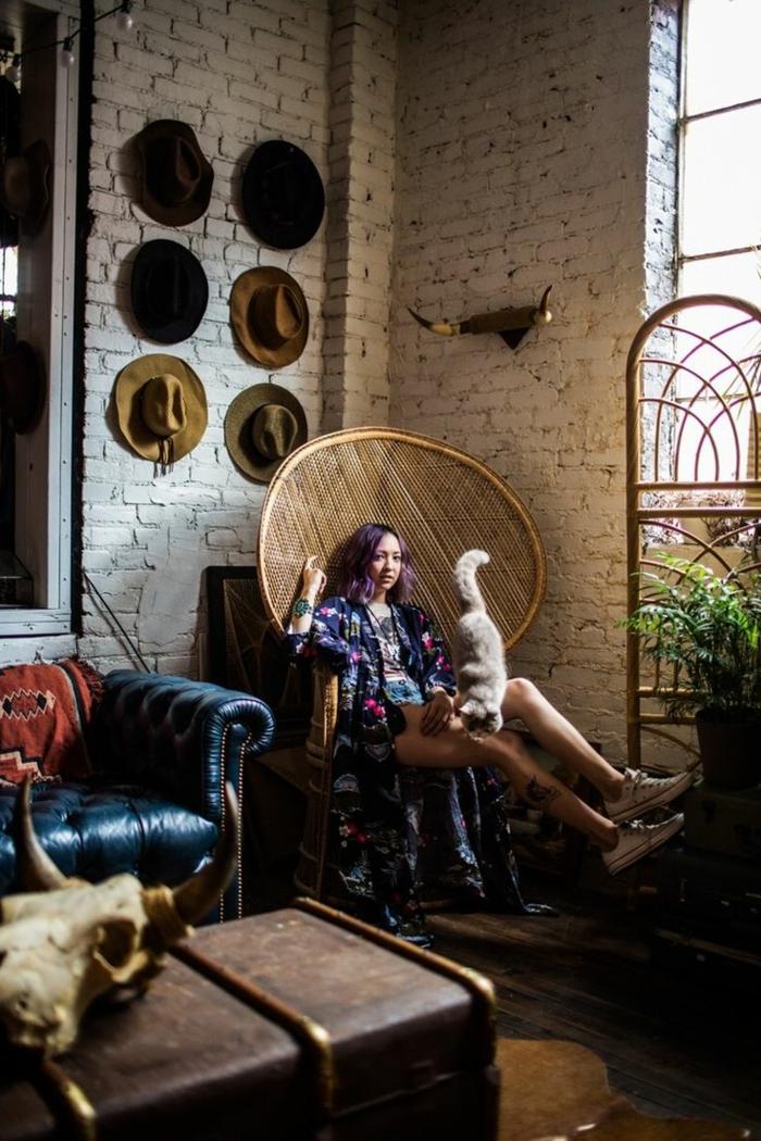 chambre hippie, murs en briques, chaise en rotin, plante verte, canapé bleu foncé