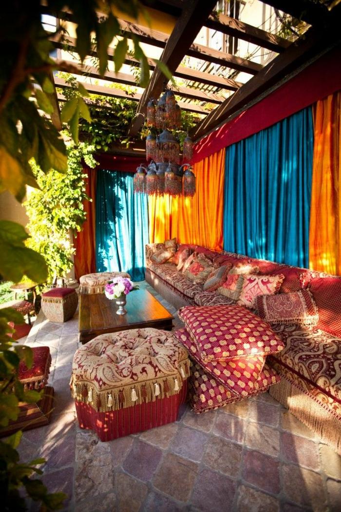 deco hippie, tabouret rouge, canapé ethnique, rideaux longs oranges et bleus