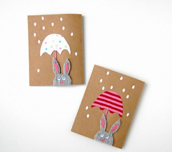 carte joyyeuses paques en papier kraft, lapin de paques en tissu gris, parapluie blanc à points et parapluie à rayures rose et rouges