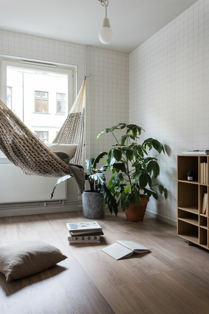 chaise balancoire, coussins gris au sol, sol en bois, plantes en pots, murs blancs
