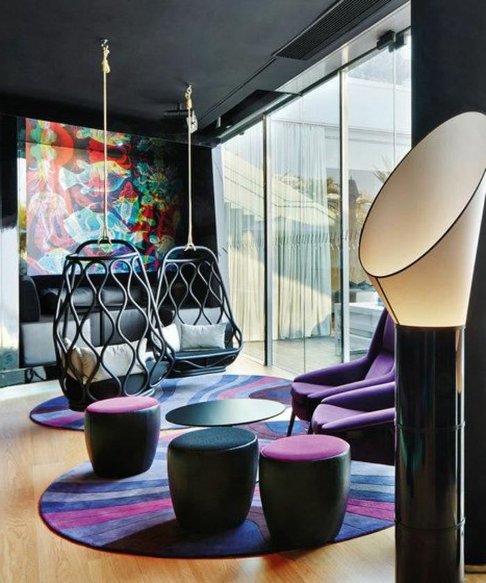 chaise ouf suspendu, deux chaises suspendues dans un salon ultra moderne avec un tableau abstrait