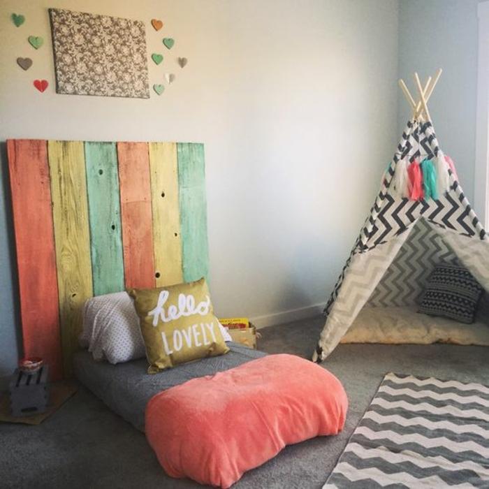mur couleur gris clair, lit bébé montessori, tête de lit de planches en bois colorées, tapis gris, titpi enfant, méthode montessori aménagement chambre enfant