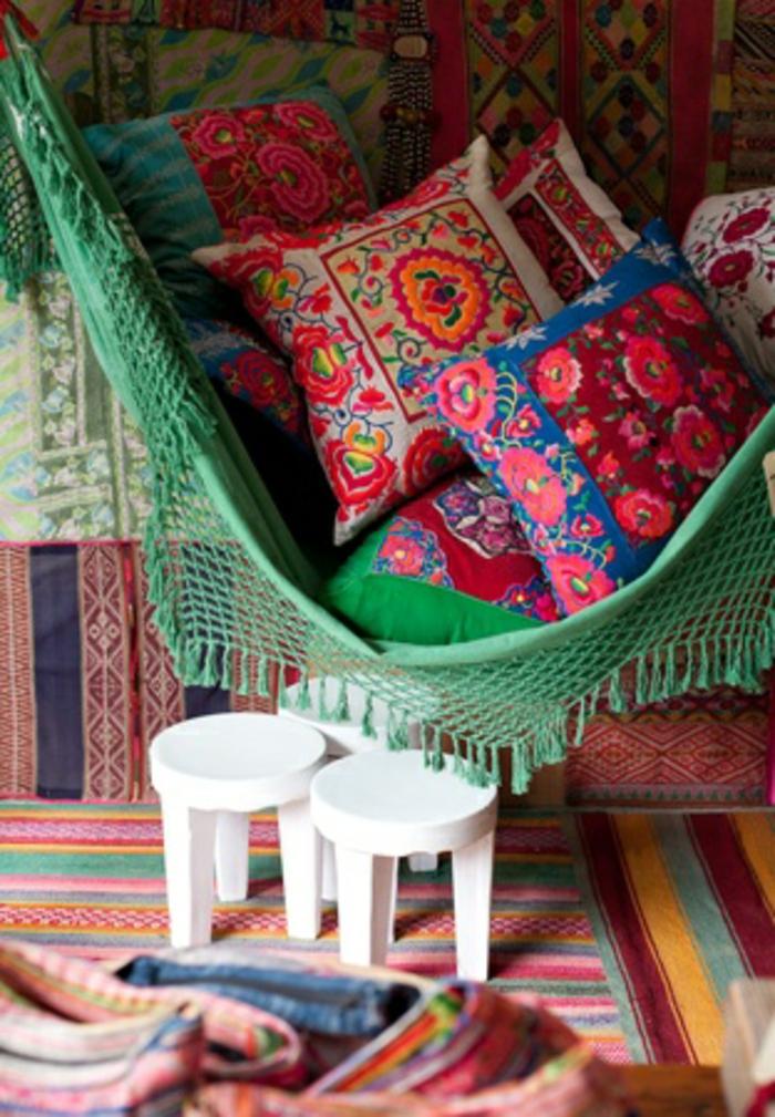 deco boheme, hamac vert avec franges, coussins décoratifs, tapis multicolore