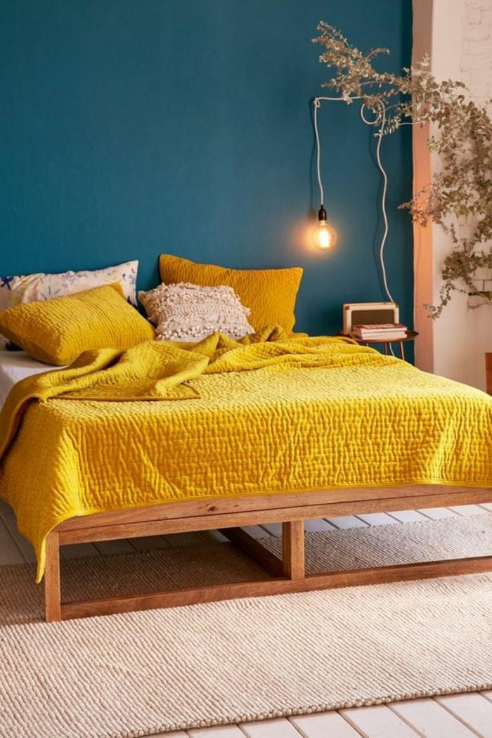 mur bleu canard, lit avec plaid jaune moutarde, ampoule et petit chevet