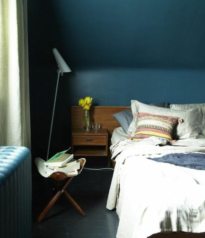 chambre mansardée, peunture murale bleu paon, linge de lit blanc cassé, coussin multicolore, parquet gris anthracite, table en bois livres, rideaux blanc cassé