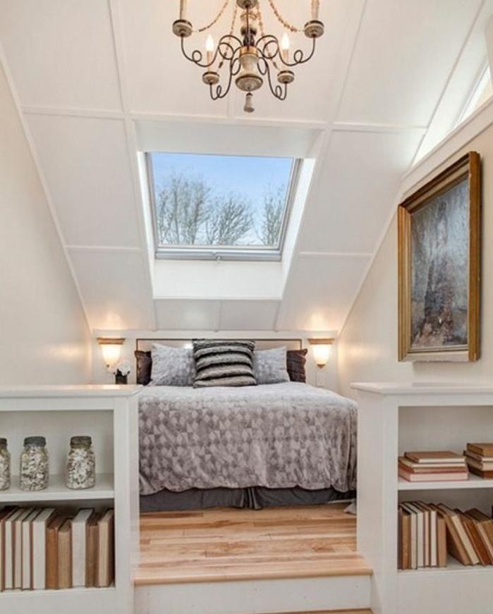 amenagement combles, peinture murale blanche, lustre élégant, parquet clair, couverture de lit grise, tableau peinture, rangement livres