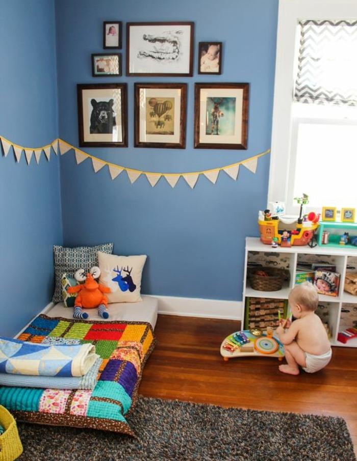 idée déco chambre enfant, mur couleur bleue, deco murale, lit bébé montessori au sol, tapis gris, meuble de rangement bas, couverture de lit multicolore, jouets, coussins