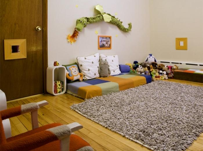 mur couleur blanc cassé, tapis gris, parquet clair, matelas à rectangles multicolores, coussins, jouets, chaise, deco murale dragon, chambre montessori