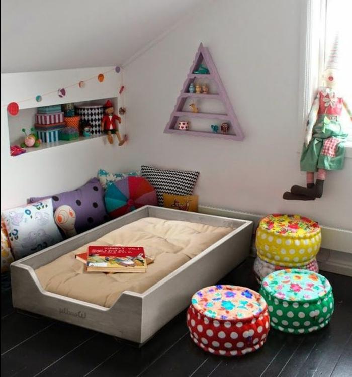 paruqet en bois foncé, lit bébé montessori, matelas, poufs multicoloresm coussins multicolores, etageres triangle, etagere encastrée dans le mur, jouets