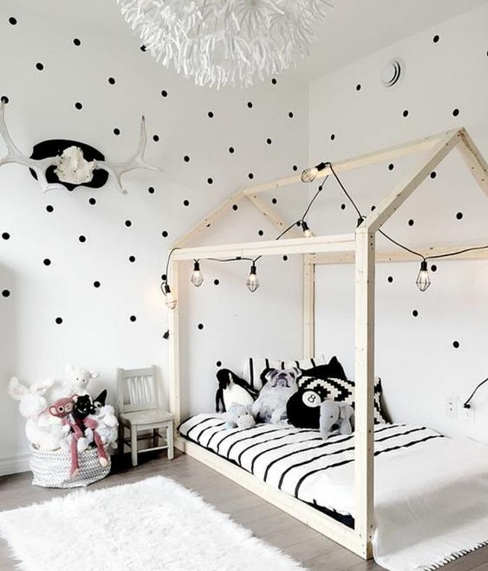 aménagement méthode montessori, lit maisonnette en bois, couverture de lit blanche à rayures noires, jouets, tapis blanc, parquet gris, couleur mur blanc à points noirs, guirlande lumineux