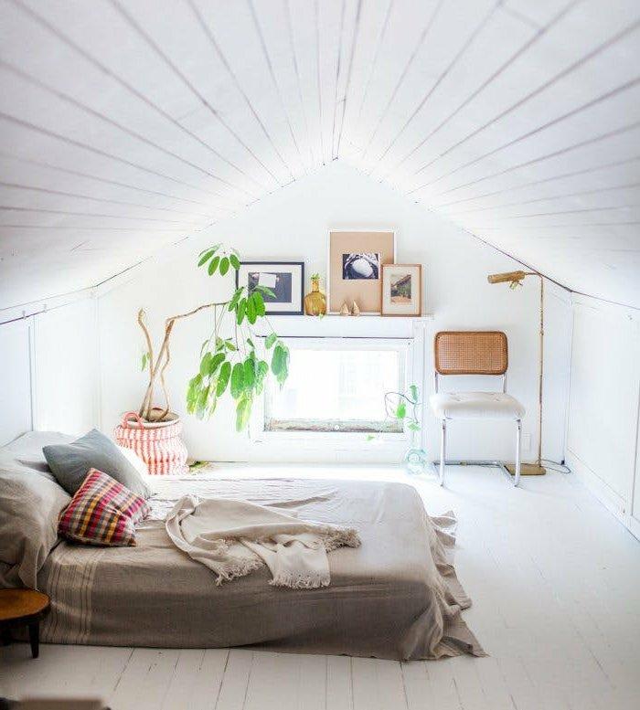 déco chambre sous pente, parquet blanc, matelas à même le plancher, linge de lit gris, coussin gris et coussin multicolore, plante, chaise, deco murale