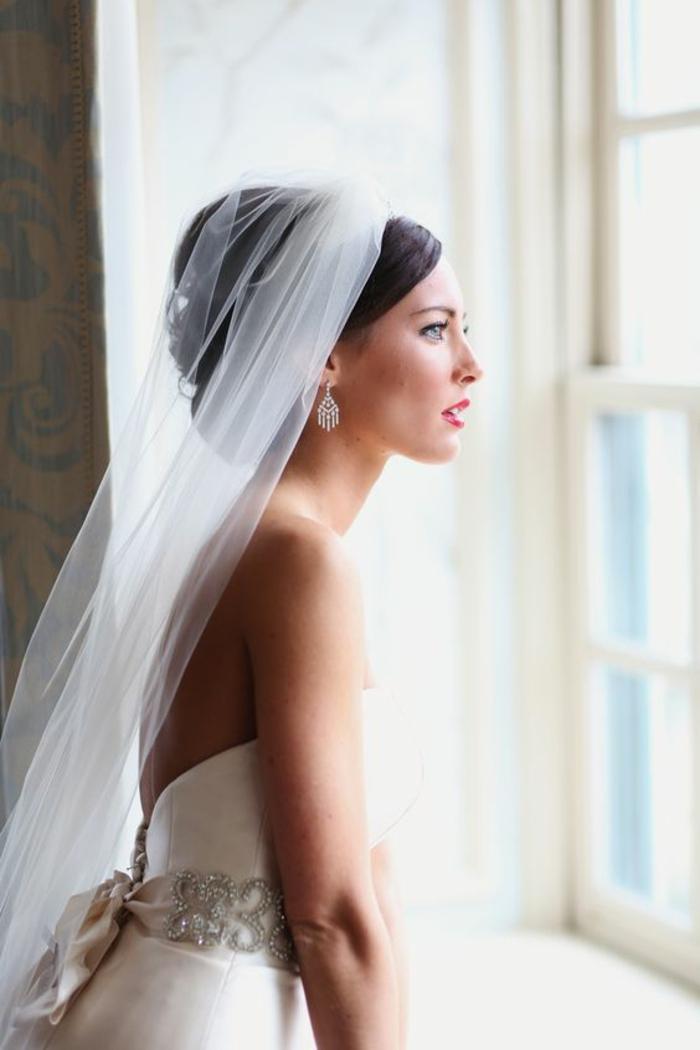 une coiffure de mariage élégante rehaussée par un voile mariée long