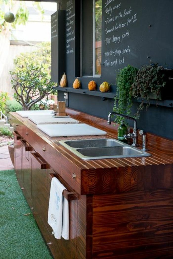 une cuisine d'extérieur en bois compact et mur en ardoise
