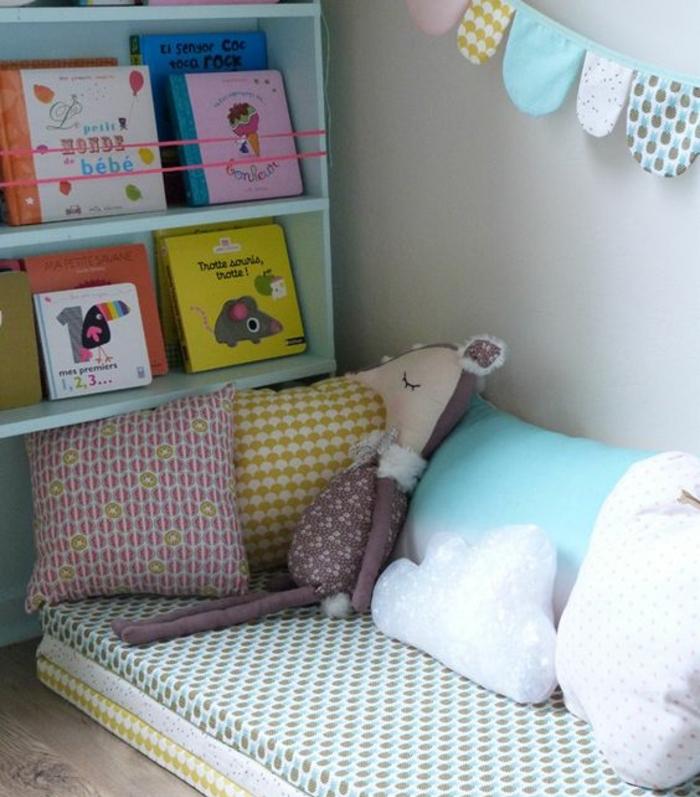 lit bébé montessori, matelas au sol, coussins multicolores, rangement etageres livres, guirlande en tissu