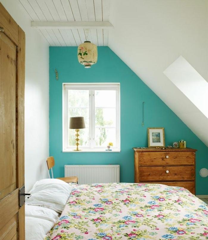 exemple de chambre mansardée, couverture de lit motifs floraux, shabby chic, armoire en bois vintage, mur d'accent bleu, suspension originale