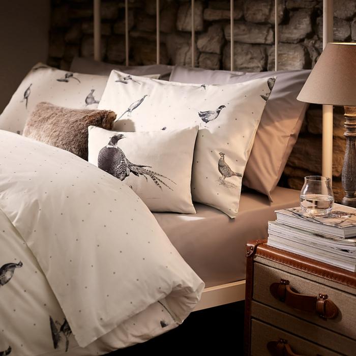 matelas nid douillet, coussins beige avec paons, armoire marron, lampe de chevet