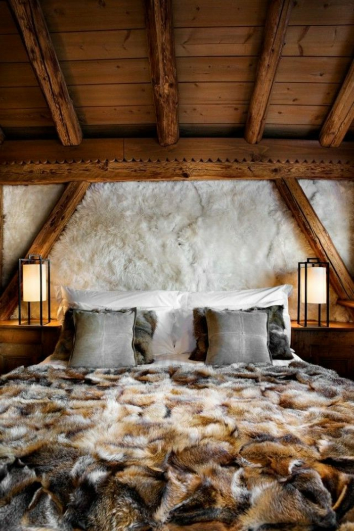 matelas nid douillet, plaid en fausse fourrure, plafond avec poutre en bois, lampe de chevet