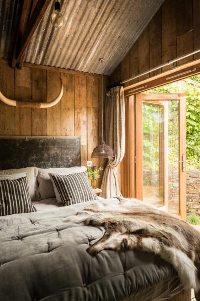 le nid douillet, plafond en bois, cornes décoratifs, grandes fenêtres, tête de lit noire