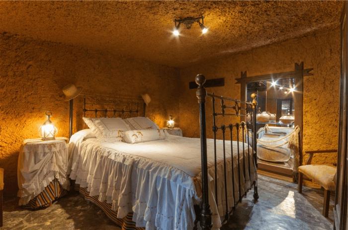 lit douillet, linge de lit blanc, cadre de lit en fer forgé, lanternes, fauteuil beige