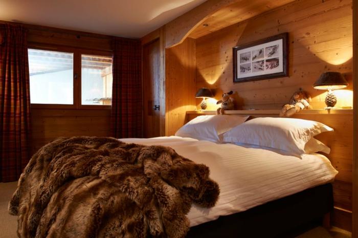 lit douillet, murs en bois, grande fenêtre, plaid en fausse fourrure, lampe de chevet