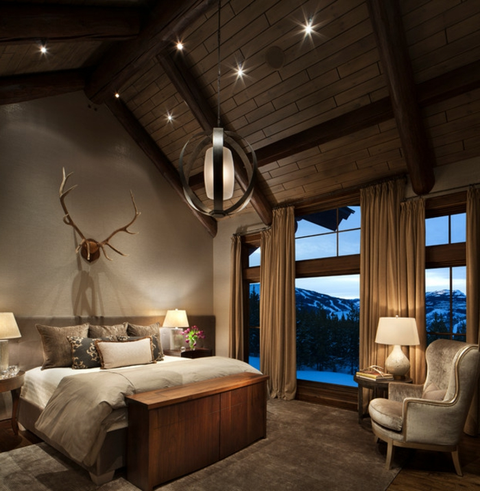 le nid douillet, cadre de lit en bois, cornes décoratifs, grande fenêtre, fauteuil vintage, lampes de chevet