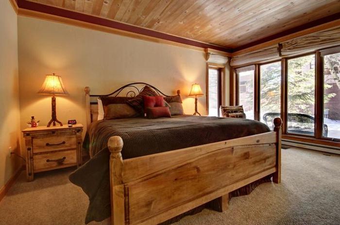 le nid douillet, cadre de lit en bois, grande fenêtre, tapis beige, lampes de chevet, coussins rouges