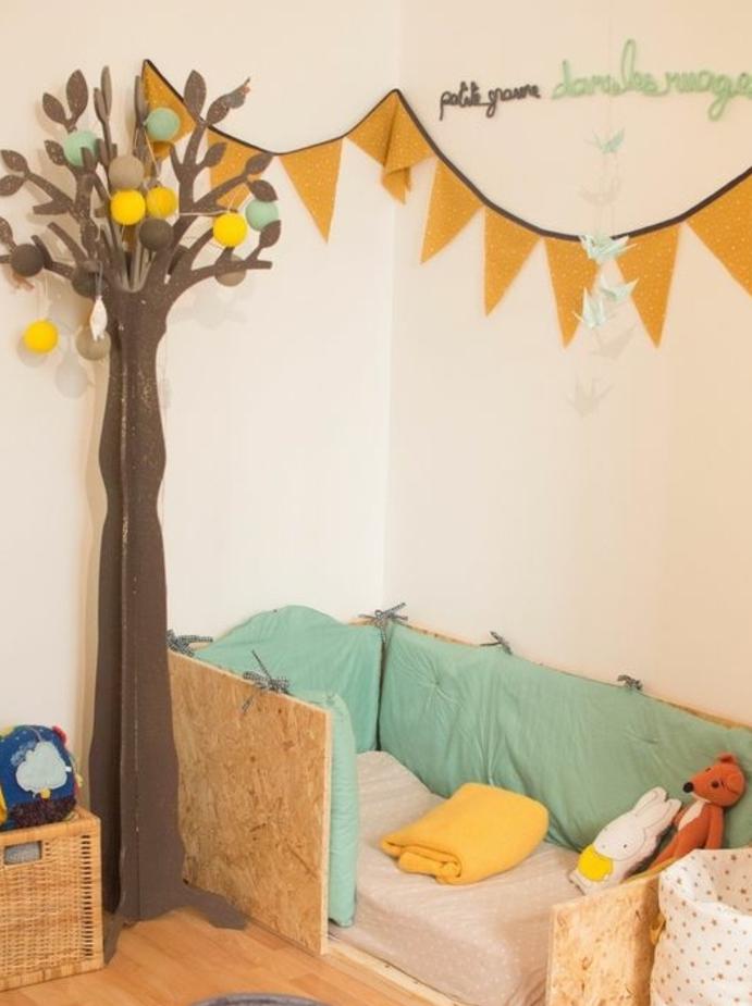 mur couleur beige, lit en bois au sol, matelas, tout de lit, parquet clair, guirlande decorative, decoration arbre en papier, aménagement chambre enfant pédagogie montessori