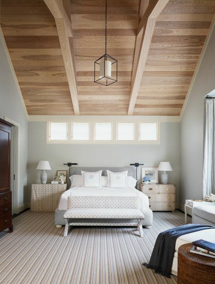 déco chambre sous pente, tapis à rayures, couleur mur blanc cassé, lit gris, linge de lit blanc, table de nuit avec tiroirs, suspension originale, armoire en bois vintage