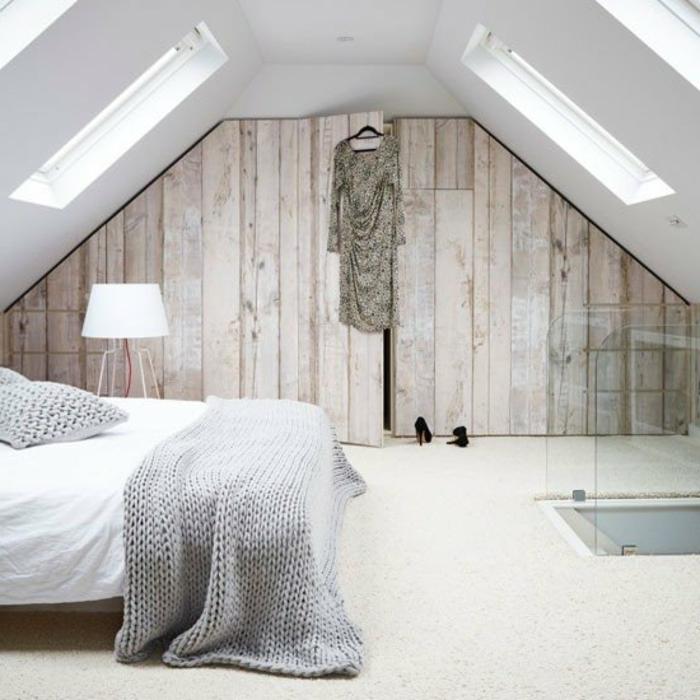 amenagement combles, dressing sous pente en bois, tapis blanc, linge de lit blanc, couverture de lit et taies d'oreiller gris