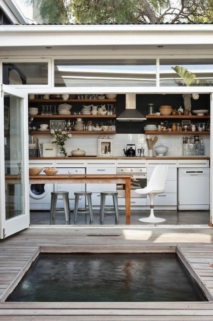 solution ingénieuse pour une cuisine d'été couverte en longueur, espace piscine avec plage en bois