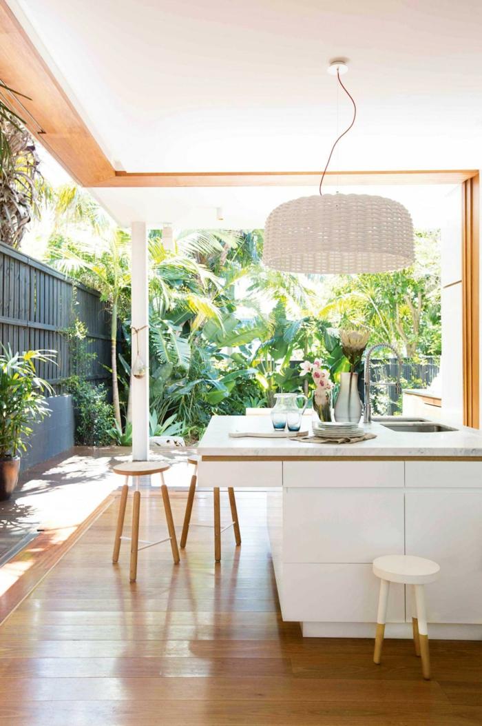 une cuisine d'été ouverte sur le jardin, îlot de cuisine blanc