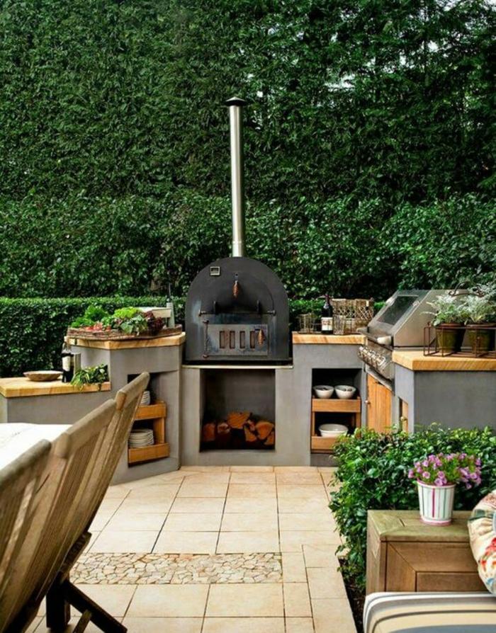cuisine d'extérieure en béton et en bois équipée d'un four à pizza