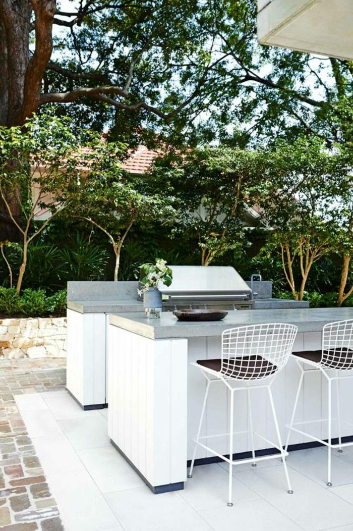 espace barbecue et cuisine d'extérieur au design épuré et élégant en blanc, des tabourets de bar métalliques